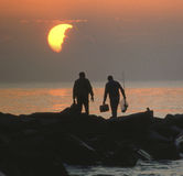 Fishermen at sunset. Silhouetted fishermen at sunset standing on rocks Stock Photo