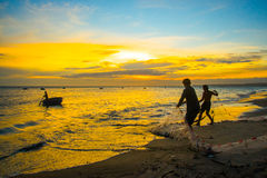 Fishermen at sunset in Vietnam. Men fish with nets, remove the fish from the sea. Stock Photo