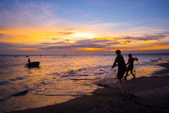Fishermen at sunset in Vietnam. Men fish with nets, remove the fish from the sea. Royalty Free Stock Image
