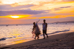 Fishermen at sunset in Vietnam. Men go on the beach with nets in hand. The silhouettes of the fishermen. Stock Photos