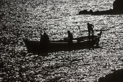 Fishermen on their boat during sunset Royalty Free Stock Photo