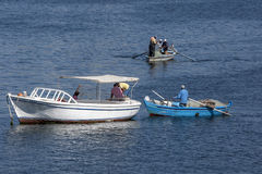 Fishermen in their boats checking nets in Alexandria Harbour in Egypt. Stock Photo