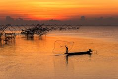 fishermen throwing fishing net from his boat early morning in the freshwater lake of Phatthalung province, Thailand Stock Photos