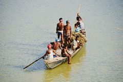 Fishermen are travelling on a boat in the river unique photo. Poor Bangladeshi fishermen are travelling with a boat in the river isolated unique editorial image stock photo