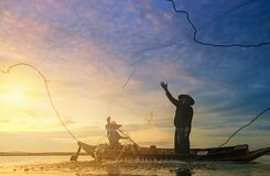 Fishermen using nets to catch fish. At the Bangpra lake during sunrise time