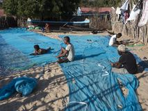 Fishermen in the village mend their nets, Madagascar royalty free stock images