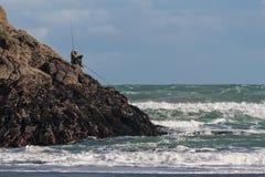 Fishermen on volcanic rocks Stock Image