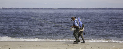 Fishermen Walk Along Beach - Panorama stock photos