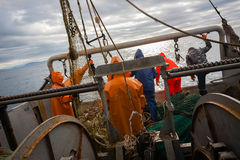 Fishermen in waterproof suits on the deck of fishing seiner Stock Image