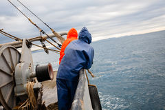 Fishermen in waterproof suits on the deck of the fishing vessel Stock Photography