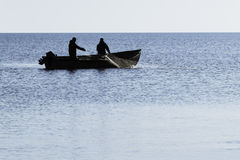 Fishermen who pull the nets. In the blue sea Royalty Free Stock Photos