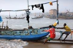 Fishermen in Winneba, Ghana. Fishermen pull a boat in Winneba, Ghana. Illegal fishing by foreign vessels threatens the traditional fishing villages in Ghana royalty free stock image