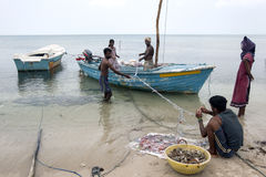 Fishermen and women attending to their nets on Delft Island in the northern region of Jaffna in Sri Lanka. Delft Island is located 10 kilometres off the coast royalty free stock photo