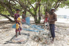 Fishermen and women preparing their fishing nets on Delft Island in the northern region of Jaffna in Sri Lanka. Stock Photos