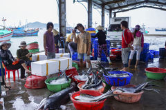 Fishermen and women sorting fish at the harbor. Royalty Free Stock Images