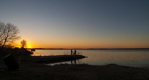 Fishermen on a wooden dock at sunrise on the lake Royalty Free Stock Photography