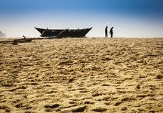 Fishermen at the work in India. Silhouettes of fishermen near the boat on the beach Royalty Free Stock Photos