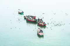Fishermen in wooden boats Stock Photos