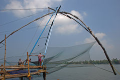 Fishermen Working with Chinese fishing nets at Fort Cochin royalty free stock image