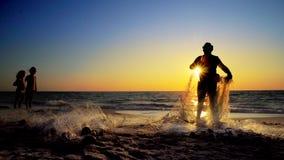 Fishermen working repairing fishing nets on ocean coast at sunset royalty free stock photo