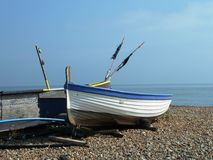 Fishermens boats on the beach. Fishermens boats on a shingle beach with a background of blue sea and sky.  Flags are flying in the breeze on the boats Stock Photos