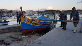 Fishermens in Marsaxlokk, Malta. Fishermens carrying a traditional boat in Marsaxlokk, Malta Royalty Free Stock Images
