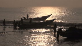 Fishermens silhouette and boats in Bengal bay sea, India stock video