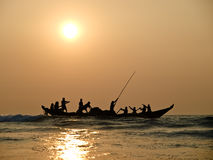 Fishers on boat in sunset on the sea Stock Image