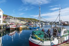 Fishers boat with two fishmen in moored in the harbor of Honningsvag city in Mageroya island.  Nordkapp Municipality in Finnmark