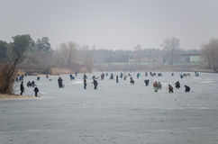 Fishers on the channel. Fishers on the frozen channel in the winter Stock Image
