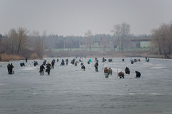 Fishers on the channel. Fishers on the frozen channel in the winter Stock Photography