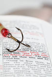 Fishers of men. Fishing hook on the Bible with focus on Matthew 4:19 where Jesus calls disciples to be fishers of men Stock Photo