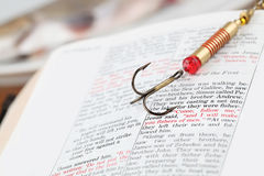 Fishers of men. Fishing hook on the Bible with focus on a very popular text in Matthew 4:19 where Jesus calls disciples to be fishers of men. All copyright items Royalty Free Stock Photos