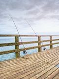Fishers rods against handrail of wooden bridge.  Fishing on harbor mole. Overcast day Stock Image
