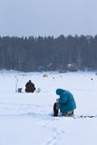 Fishers on the snow-covered field near the forest Royalty Free Stock Photo