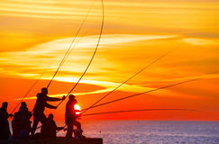 Fishers at sunset Stock Photo