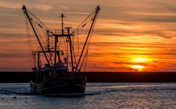 Fishersboat entering harbor during sunset royalty free stock photography
