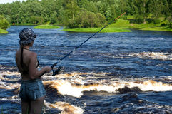 Fisherwoman. Young girl fishing on the river Royalty Free Stock Photo