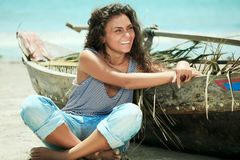 Fisherwoman. Young beautiful fisherwoman with boat on the beach royalty free stock photography