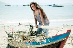 Fisherwoman. Young beautiful fisherwoman with boat on the beach stock photos