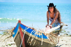 Fisherwoman. Young beautiful fisherwoman with boat on the beach stock images