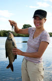 Fisherwoman. Holding a bream on the river stock images