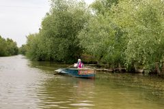 Fisherwoman manages a boat with oars on Danube River. Vilkovo, Ukraine - May, 26, 2018: Fisherwoman manages a boat with oars on Danube River Royalty Free Stock Images