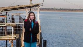 Fisherwoman on the phone near her fishing hut stock photography