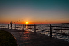 Fisherwoman at sunset. Fisherwoman in the summer evening at sunset in the mouth of the river stock photo