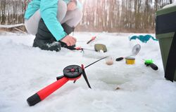 Fisherwoman with winter rods. On a frozen river stock photography
