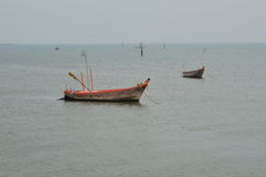 Fishery boat floating on the dull sea Stock Images