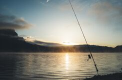Fishery relax concept, outline fishing rod at sunrise sunlight, hobby sport on mist evening lake, catch fish