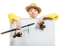 Bored woman with fishing rod holding board Stock Photo