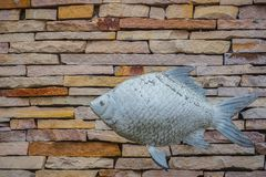 Fishes and pattern of old decorative stone wall background. Vintage stone wall Texture in weathered and have fish sculptures for. Design background. Featured royalty free stock photo